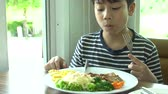 comida chinesa : little Asian boy eating steak with vegetable Salad at restaurant with smile face