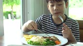 kés : little Asian boy eating steak with vegetable Salad at restaurant with smile face