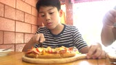 conhecimento : Little asian child eating pizza at restaurant .happy asian boy enjoy at your meal. Stock Footage