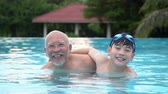 четыре человека : Slow motion of Happy asian family playing in pool, Asian grandchildren and grand parents swimming in pool.