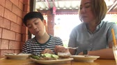 Happy Asian mother with her son eating lunch at home,happy asian family enjoy with meal Стоковые видеозаписи