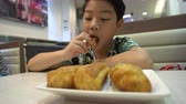Happy asian preteens boy enjoy eating in morning breakfast. Стоковые видеозаписи
