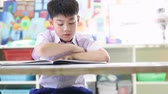 Asian child in student uniform reading and writing to do homework of the school . Стоковые видеозаписи