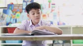 Asian child in student uniform reading and writing to do homework of the school . Dostupné videozáznamy