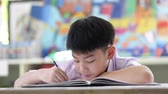 Asian child in student uniform reading and writing to do homework of the school . Vídeos