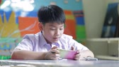 Happy Asian child using a digital tablet .
