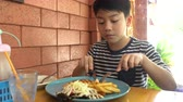 Little asian child eating pizza at restaurant .happy asian boy enjoy at your meal. Vídeos