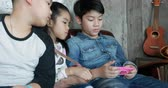Happy asian boy and girl playing smart phone and tablet in camping area Стоковые видеозаписи