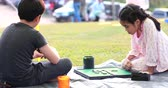 Happy asian boy and girl playing board game in camping area Стоковые видеозаписи