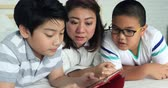 Интернет : Happy asian family mother with her son playing game with tablet computer on the bed at home . Стоковые видеозаписи