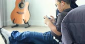 gitara : leisure, children, technology and people concept - smiling asian boy with smartphone and headphones listening to music or playing game at home