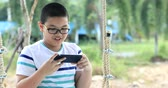 hinta : Happy asian child hand holding mobile phone on swing chair with smile face.