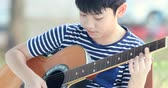 akustik : Little asian boy is playing the guitar