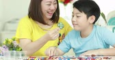 barátság : Happy asian family mother and son playing plastic block together . Stock mozgókép