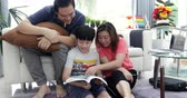 bible : Happy asian family father mother and son reading education book together with smile at home.