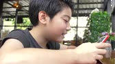 czytanie : Slow motion of Young asian boy playing with a cell phone or smartphone at cafe with smile face . Wideo