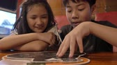 czytanie : Happy asian child in a cafe or restaurant choose a menu of drinks and food.  Slow motion of brother and sister at restaurant.