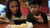 czytanie : Happy asian child watching on mobile phone and enjoy eating potato fires, Slow motion of brother and sister at restaurant.
