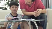 ailelerin : Asian Father and son doing homework on the table in the living room .