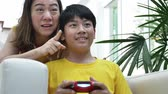 otec : Asian mother and son playing video game at home together.4K Slow motion of happy family playing with smile face.