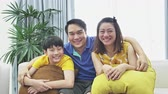 ailelerin : Slow motion of asian family father mother and son on couch, Looking at camera  with smile face.