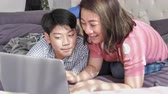 ailelerin : Happy family Mother and Son watching on laptop computer with smiley face, Slow motion 4K  asian family rest on bed with laptop computer