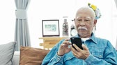 czytanie : Asian Senior man with white mustache using smart phone or tablet at home, Happy grandfather with technology in hand .Slow motion 4K, Dolly shot. Wideo