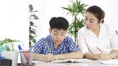 czytanie : Young asian mother teaching son at home. Asian mother with son doing homework on table with smile face. Dolly shot 4K Wideo