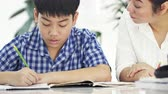 книги : Young asian mother teaching son at home. Asian mother with son doing homework on table with smile face. Dolly shot 4K Стоковые видеозаписи