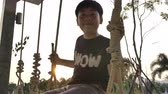 neşe : Portrait of asian child boy playing swing with sunset flare at home, Handheld Slow motion teen on swing with smile face