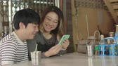 telefone : Asian mother and son watching on mobile phone together with smile face.