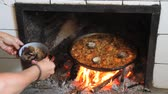 rice pan : Woman Taking clams seafood paella cooked on a wood fire Stock Footage