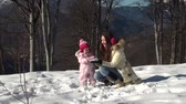 caucasian : Happy mother playing snowballs with his daughter