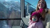 young mother with her little daughter riding on cableway in the mountains on a sunny day in winter. Slow motion Стоковые видеозаписи