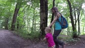 Mom walks her daughters hand in the woods. Family walk in the woods. Trips to nature. Fresh and healthy air in the coniferous forest. Slow motion. Full HD. 1920x1080