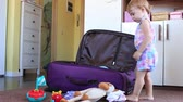 small child puts clothes and toys in the suitcase Стоковые видеозаписи