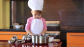 little cute girl in chef suit playing in the kitchen with a ladle and saucepan Стоковые видеозаписи