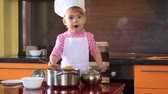 small charming child in chef suit arranges the pasta on plates in the kitchen Стоковые видеозаписи