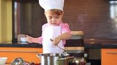 small charming child in chef suit sprinkles sugar food in the kitchen Стоковые видеозаписи