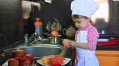 cute little baby dressed as a cook helps mum to cleans tangerine