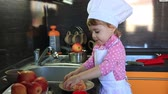 cute little baby dressed as a cook helps mum in the kitchen Стоковые видеозаписи