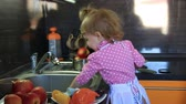 cute little baby dressed as a cook wash in the sink toys in the kitchen. Стоковые видеозаписи
