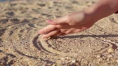 Female hand drawing infinity sign on the sand.