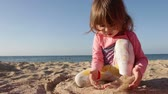 beautiful little girl is playing with sand on the beach on the background of the sea and blue sky
