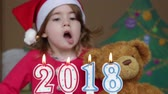 четыре человека : Pretty little girl in a Santa Claus hat blowing out candles - closeup shot. conceptual sign 2018