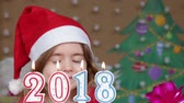Pretty little girl in a Santa Claus hat blowing out candles - closeup shot
