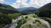 Aerial flight with drone DJI over beautiful green mountains and river. 4k