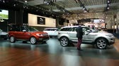 kompaktní : Two men checking a Range Rover Evoque compact SUV on display at the 2014 Brussels motor show.