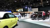 kompaktní : Opel Adam compact city car and Opel Mokka compact SUV on display at the 2014 Brussels motor show. A group of people is discussing the cars in the background.