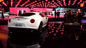 kompaktní : White Alfa Romeo 4C compact sports car with two girls sitting behind an information desk on the right during the 2015 Brussels motor show. Dostupné videozáznamy